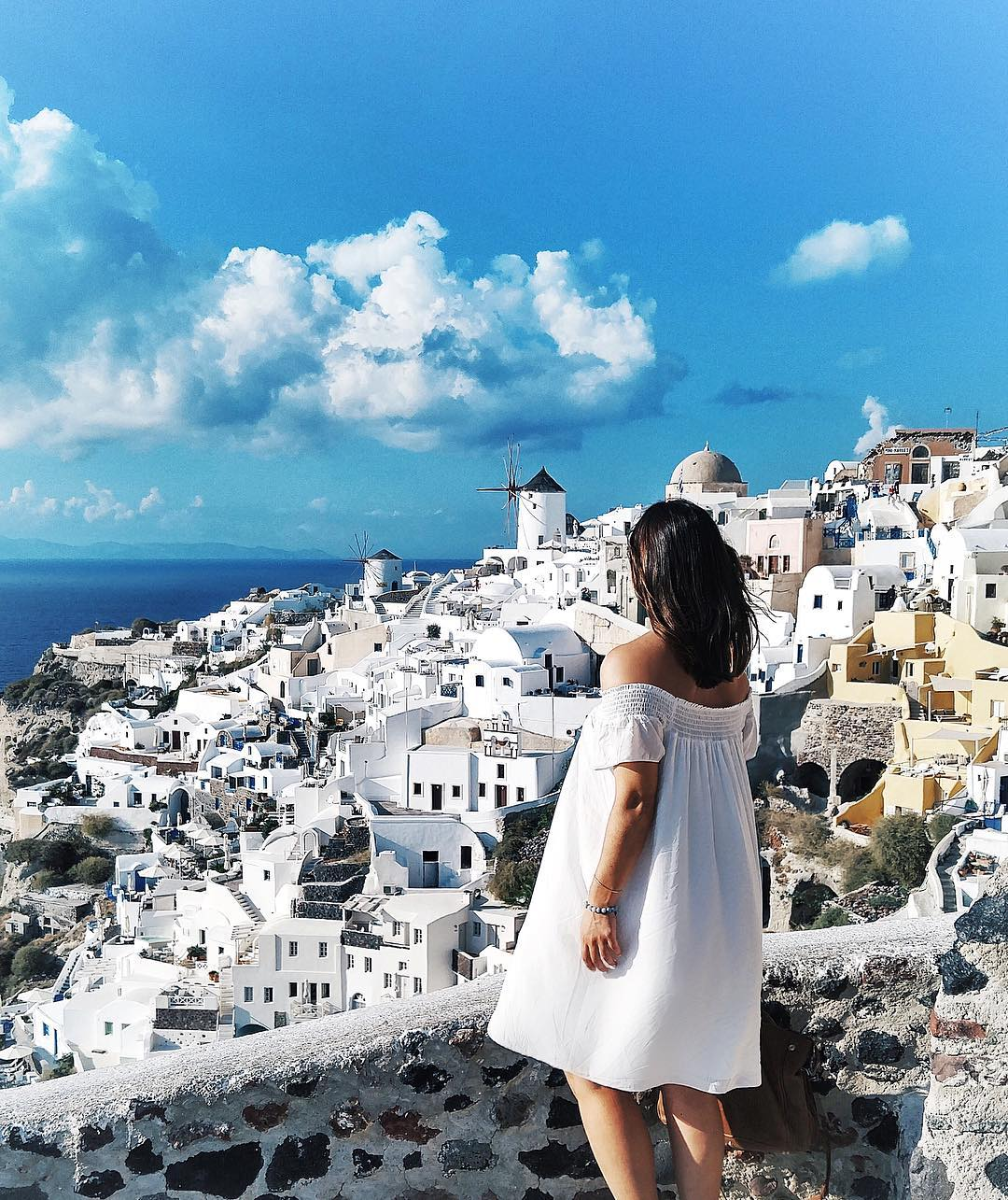 To Vogue or Bust in an Aritzia off the shoulder dress in Oia, Santorini, Greece