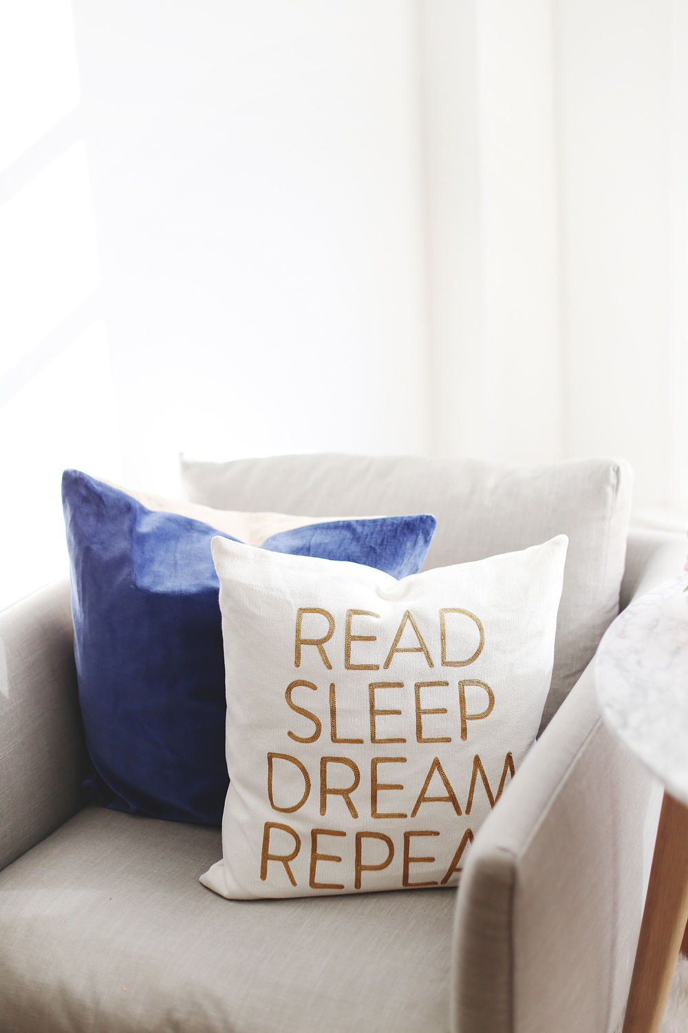 To Vogue or Bust shares how to start a book club in an airy minimalist studio space featuring Chapters books, Chapters decor, Chapters pillows