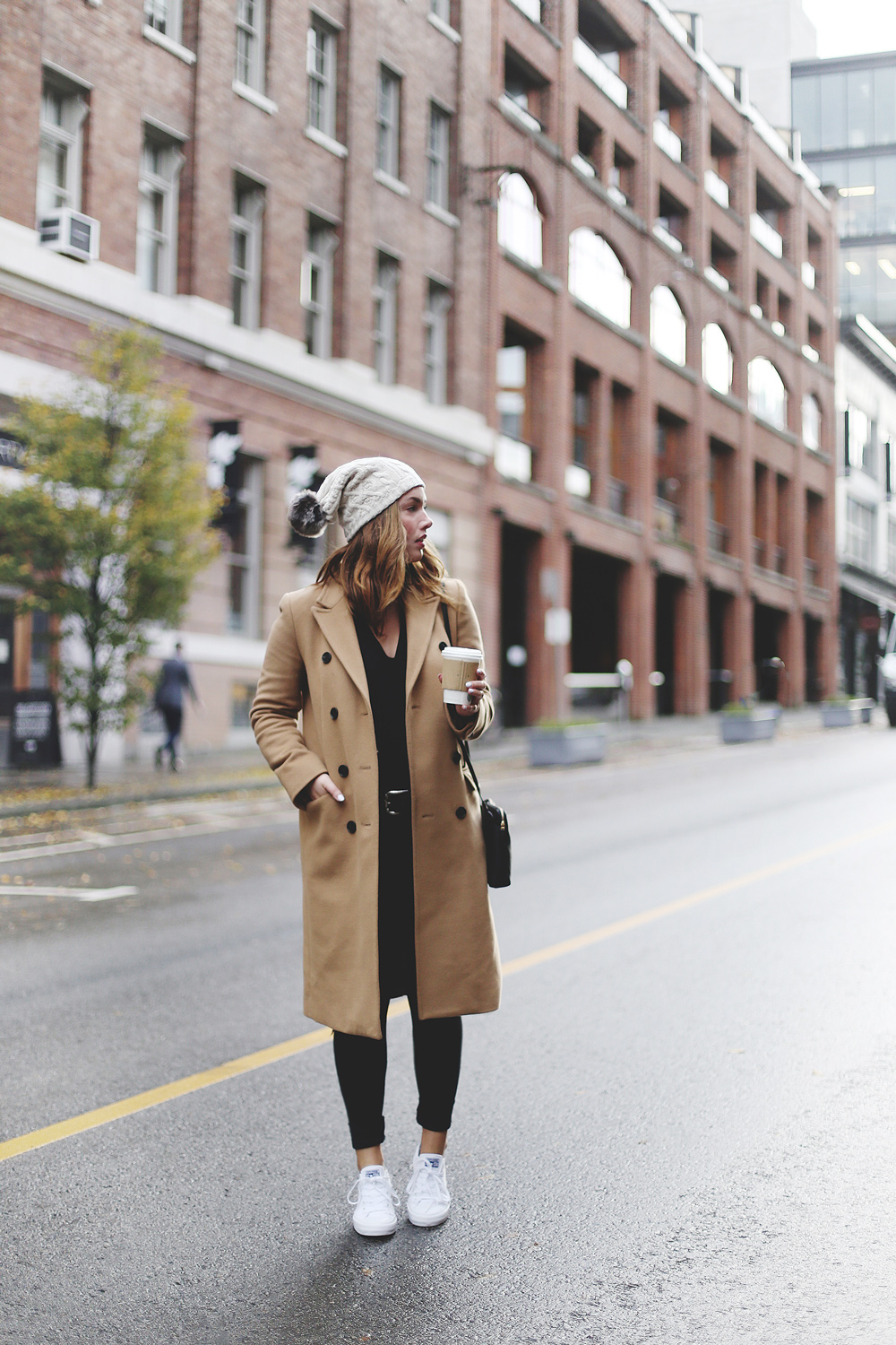 To Vogue or Bust shares ways to style your converse sneakers in white Converse All Stars, Aritzia camel coat, James Jeans black skinny jeans, Aritzia black leather bag and a Tilley Hats beanie