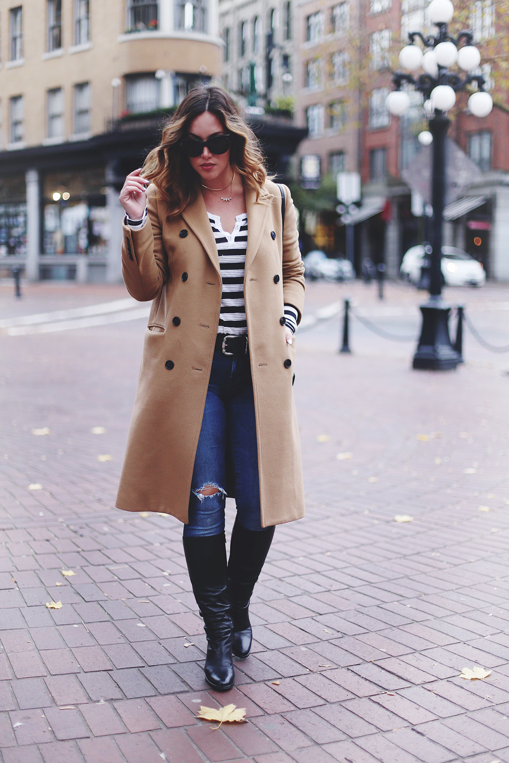 To Vogue or Bust shares camel coat outfit ideas in a camel Aritzia wilfred coat, Mavi skinny jeans, striped Gentle Fawn top, La Canadienne boots and Celine sunglasses in Gastown, Vancouver